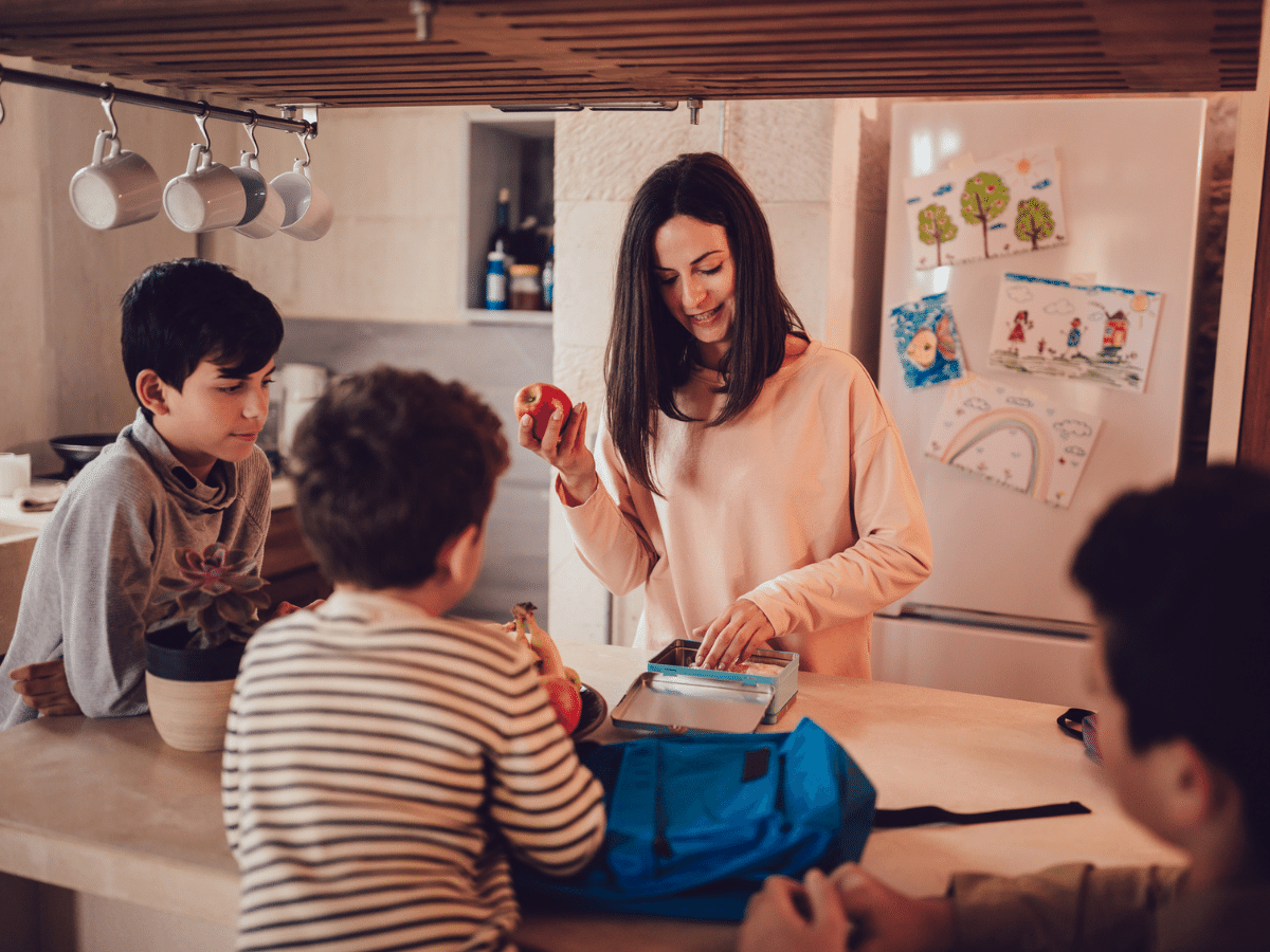 Mother preparing lunch boxes with healthy food and snacks for sons before going to school