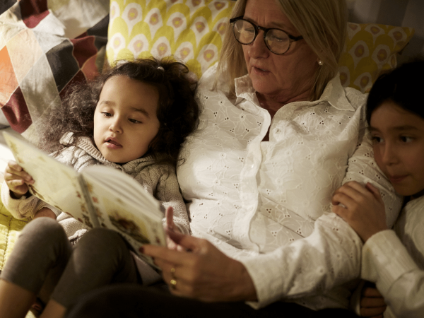 High angle view of grandmother reading book to granddaughters while lying on bed at home