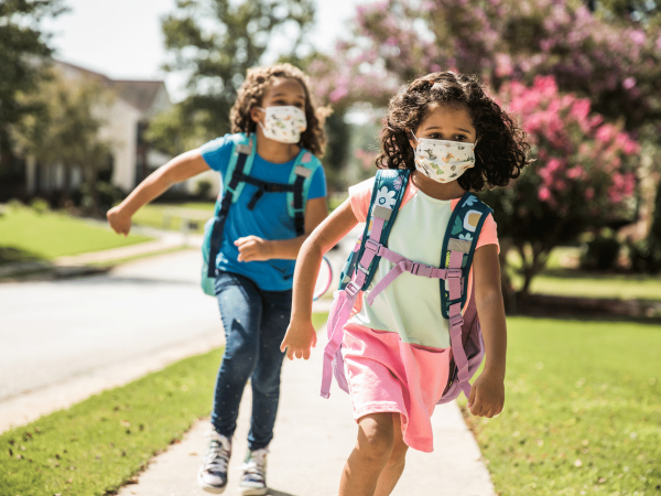Young girls wearing protective masks and backpacks running on sidewalk