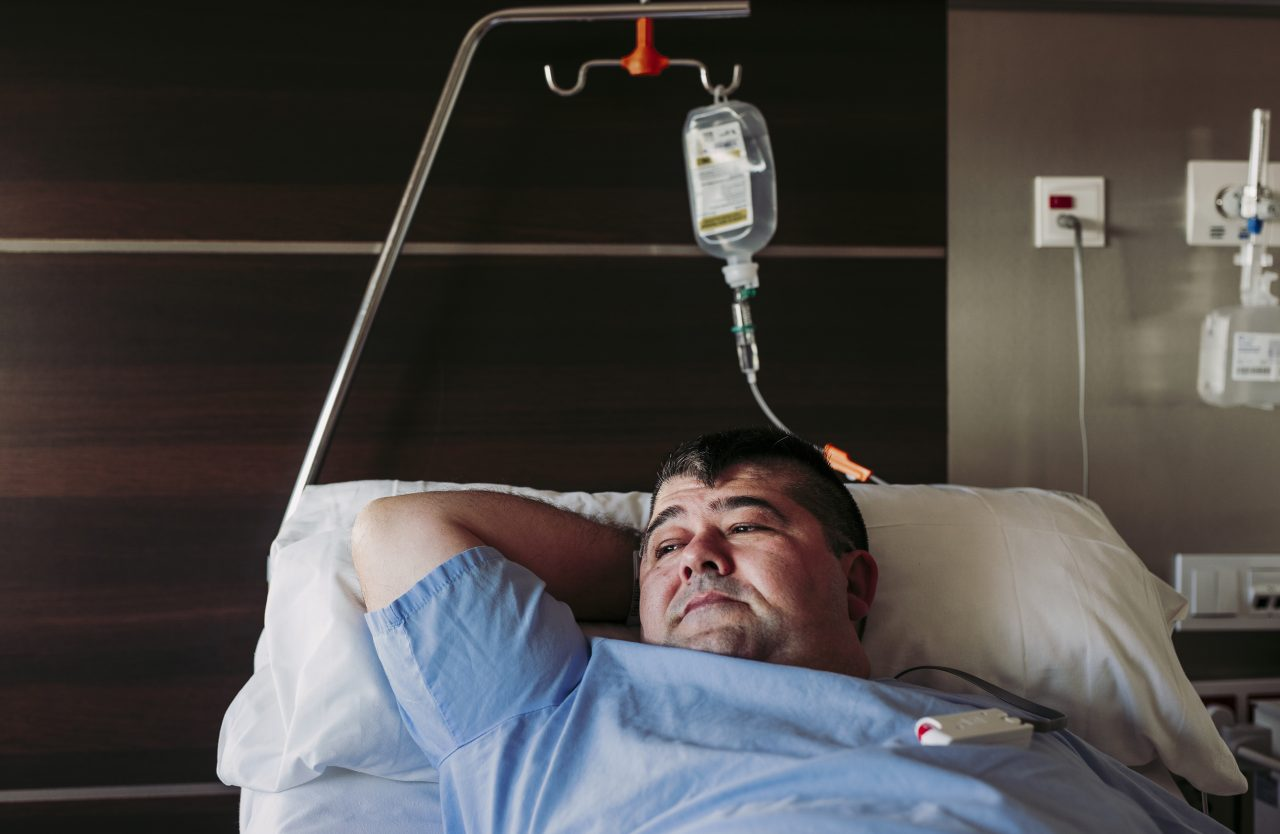 man laying in hospital bed