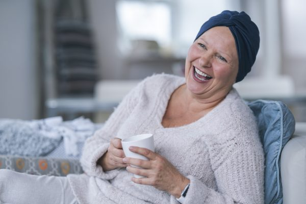 Woman who has lost her hair due to cancer treatment is smiling while holding a mug of coffee.