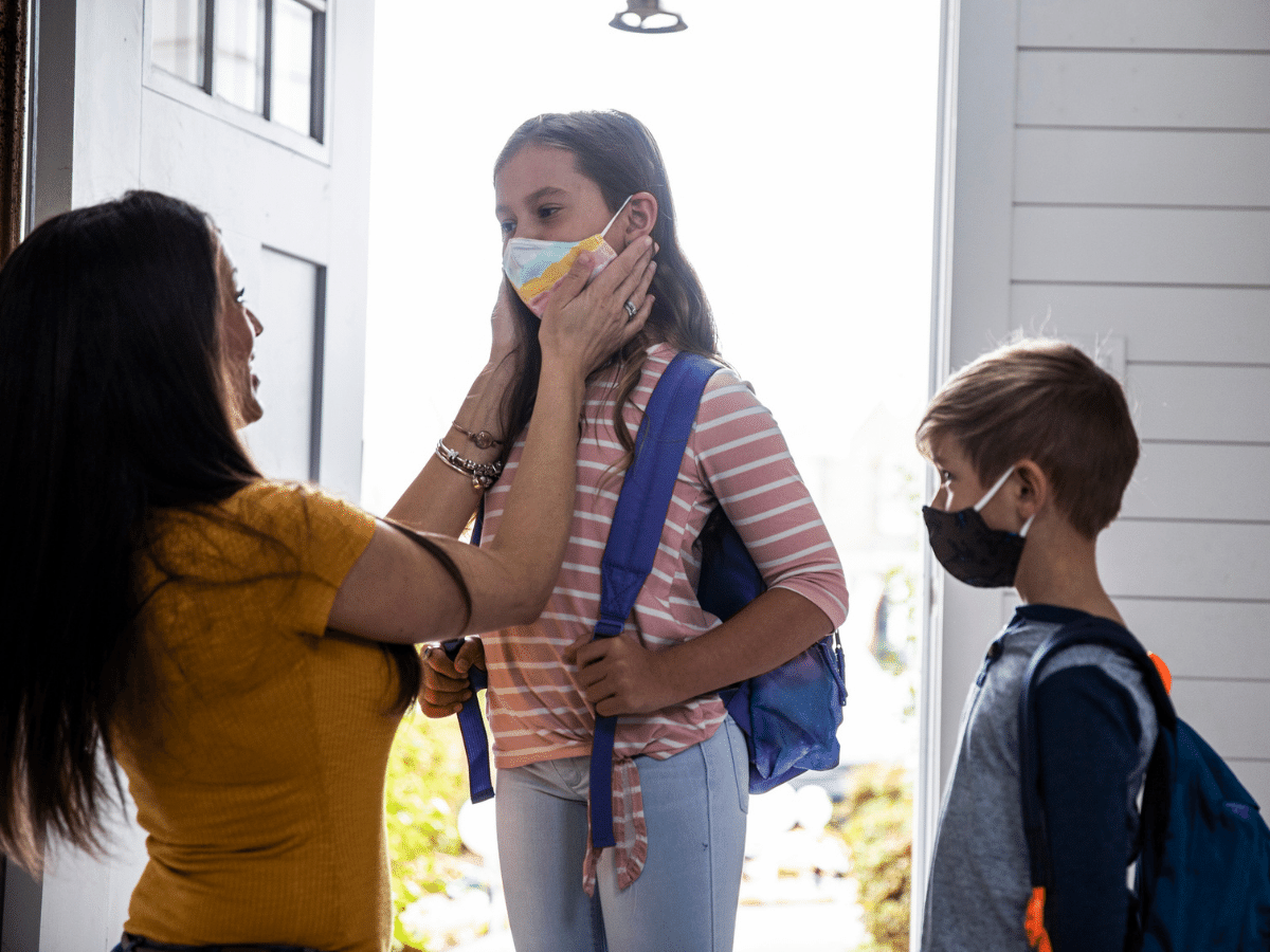 Mother helping two young children get ready for school, putting cloth masks on before leaving the house