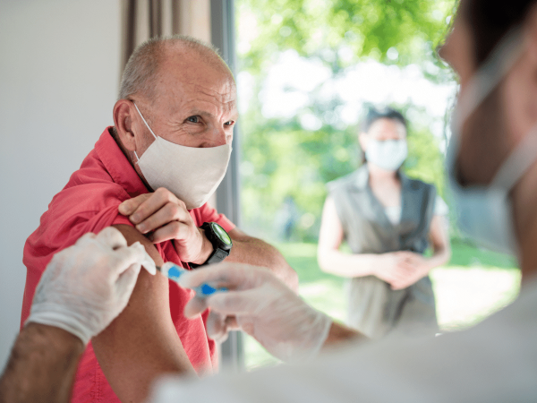 Senior male wearing a mask in a doctor's office receiving a vaccination