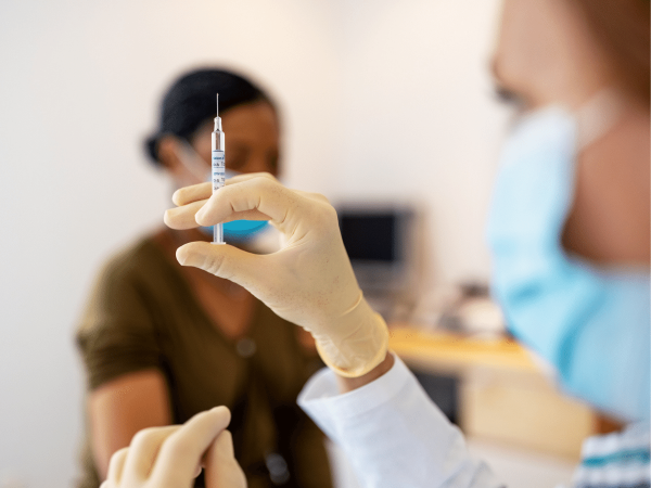 Nurse in foreground prepares a syringe, patient, out of focus in background waits to get vaccinated.