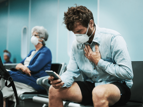 Young man wearing a mask holds his chest in pain while looking at a smartphone in a waiting room.