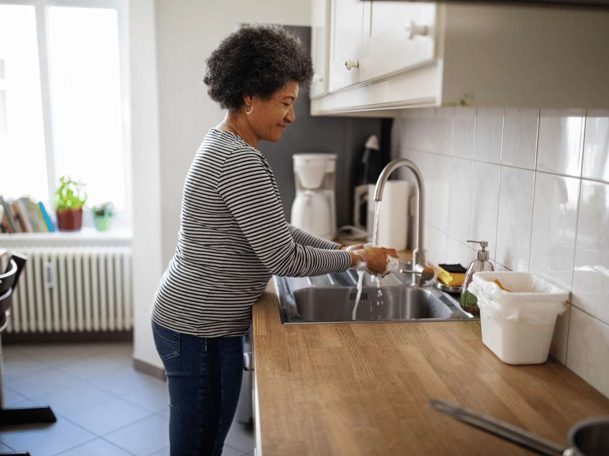 Middle-aged woman at home washing her hands in the kitchen sink