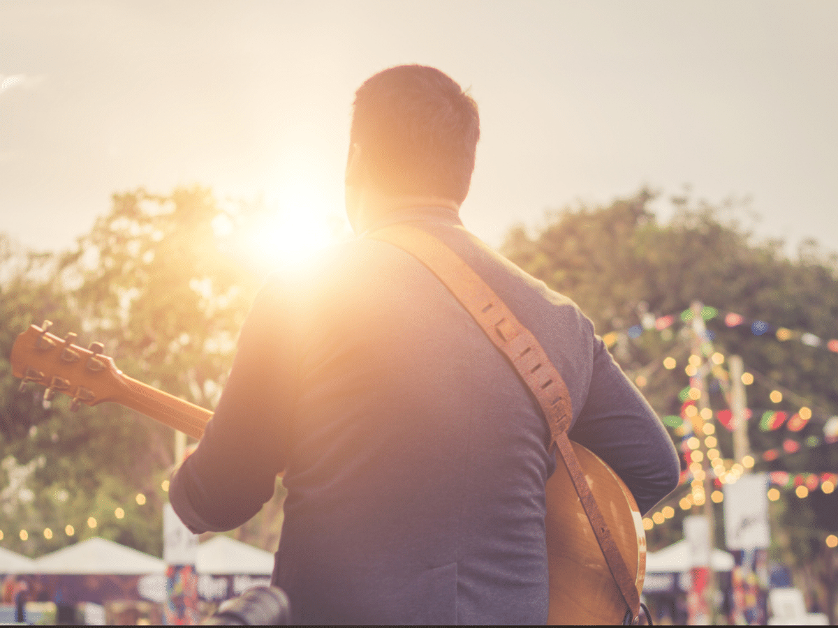 Musician playing guitar on stage at sunset