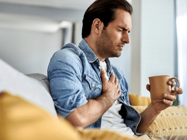 Young man at home sitting on couch drinking tea, holds chest in pain