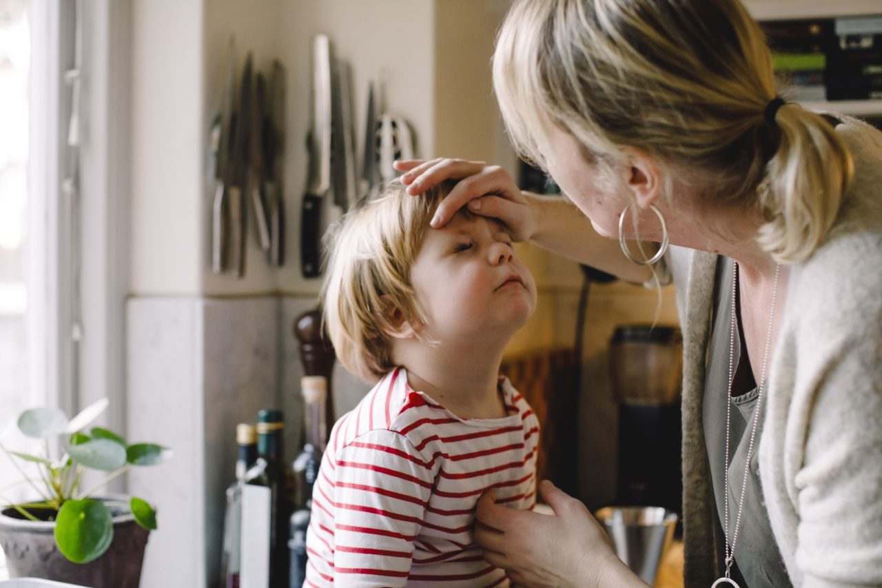Caring mother looking at daughter's eye in kitchen