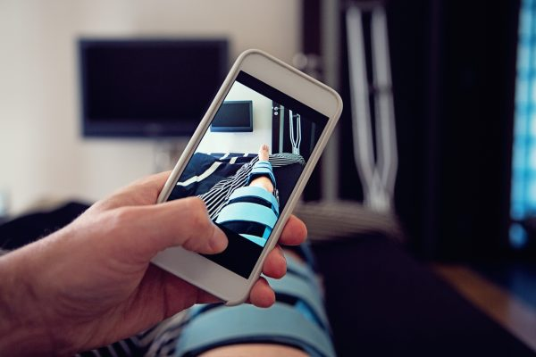 Man lying in hospital bed and take pictures of his injured knee.