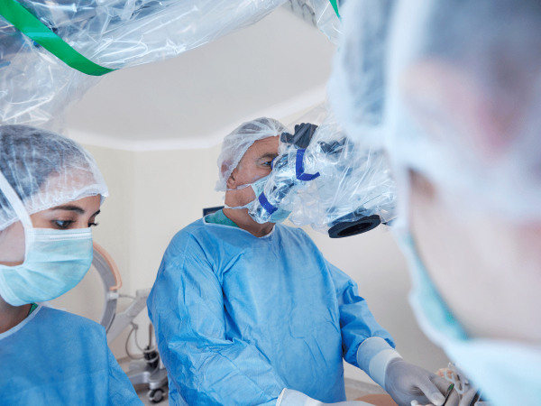 Surgeon wearing protective equipment uses a robotic surgery device in an operating room
