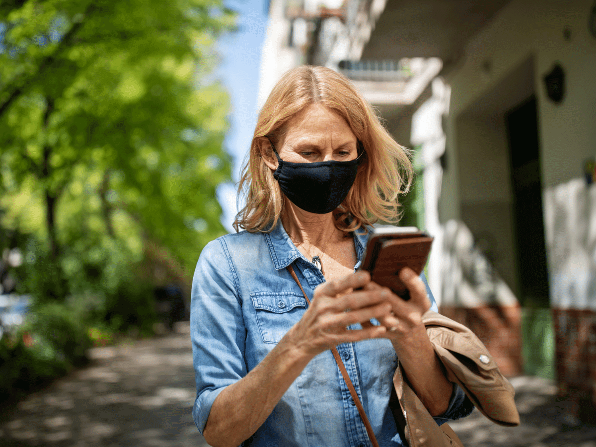 Middle aged woman wearing a mask outside while looking at her smartphone