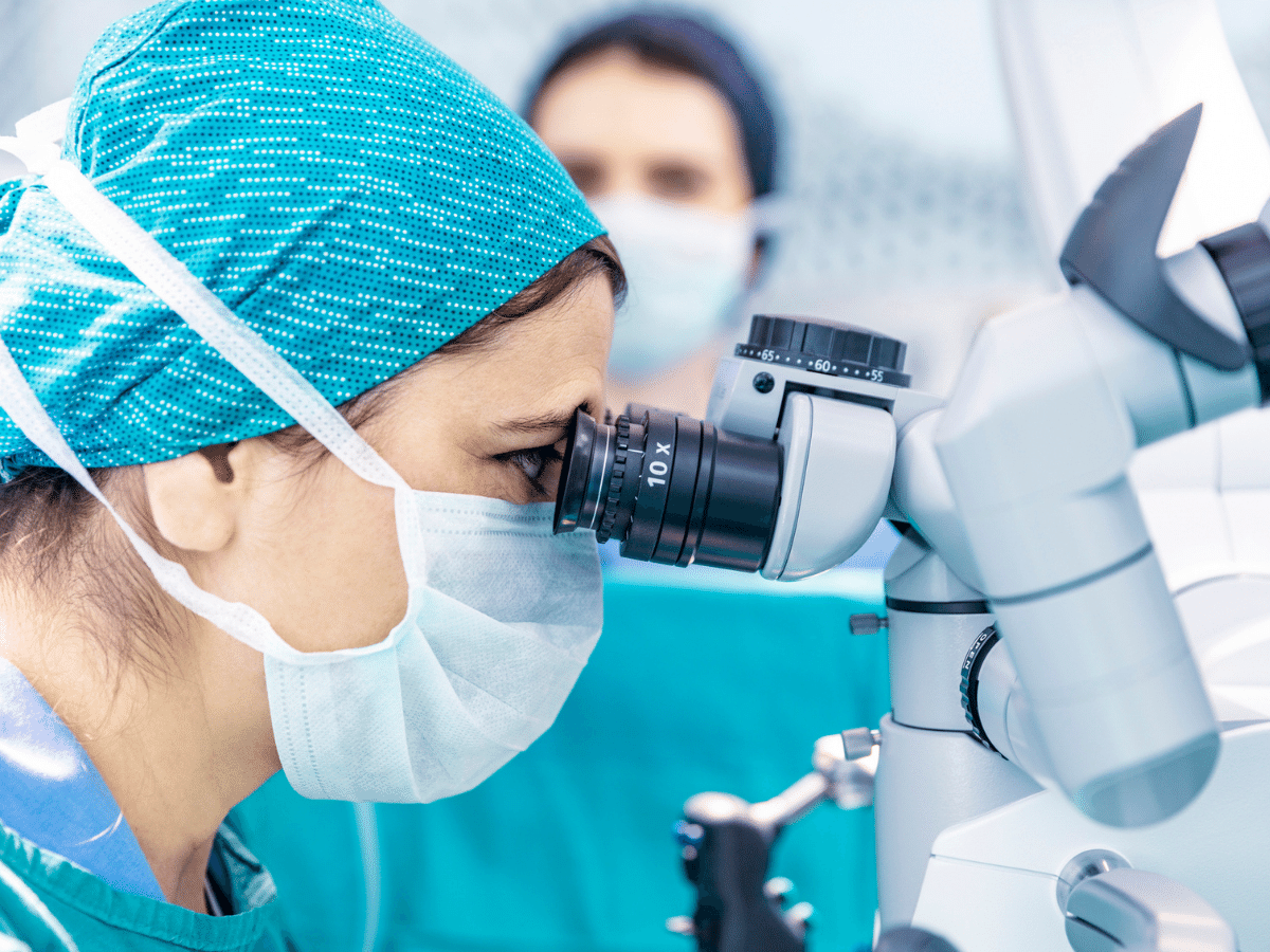 doctor wearing protective face mask and surgical cap, looking into the eye piece of a robotic surgery device.