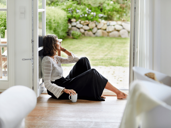 Woman sitting on the floor inside her house looking outside
