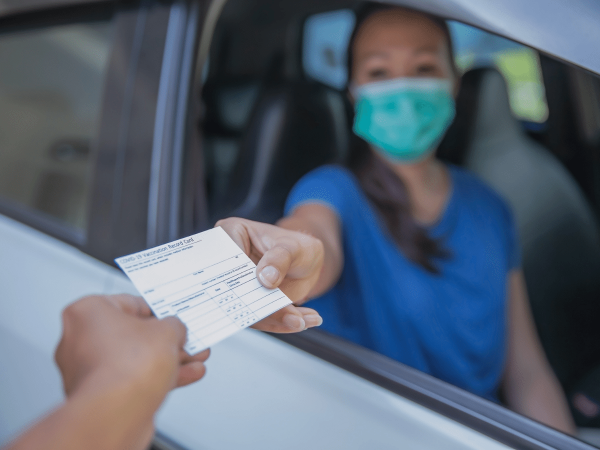 Woman wearing a mask showing her COVID-19 vaccine card to someone