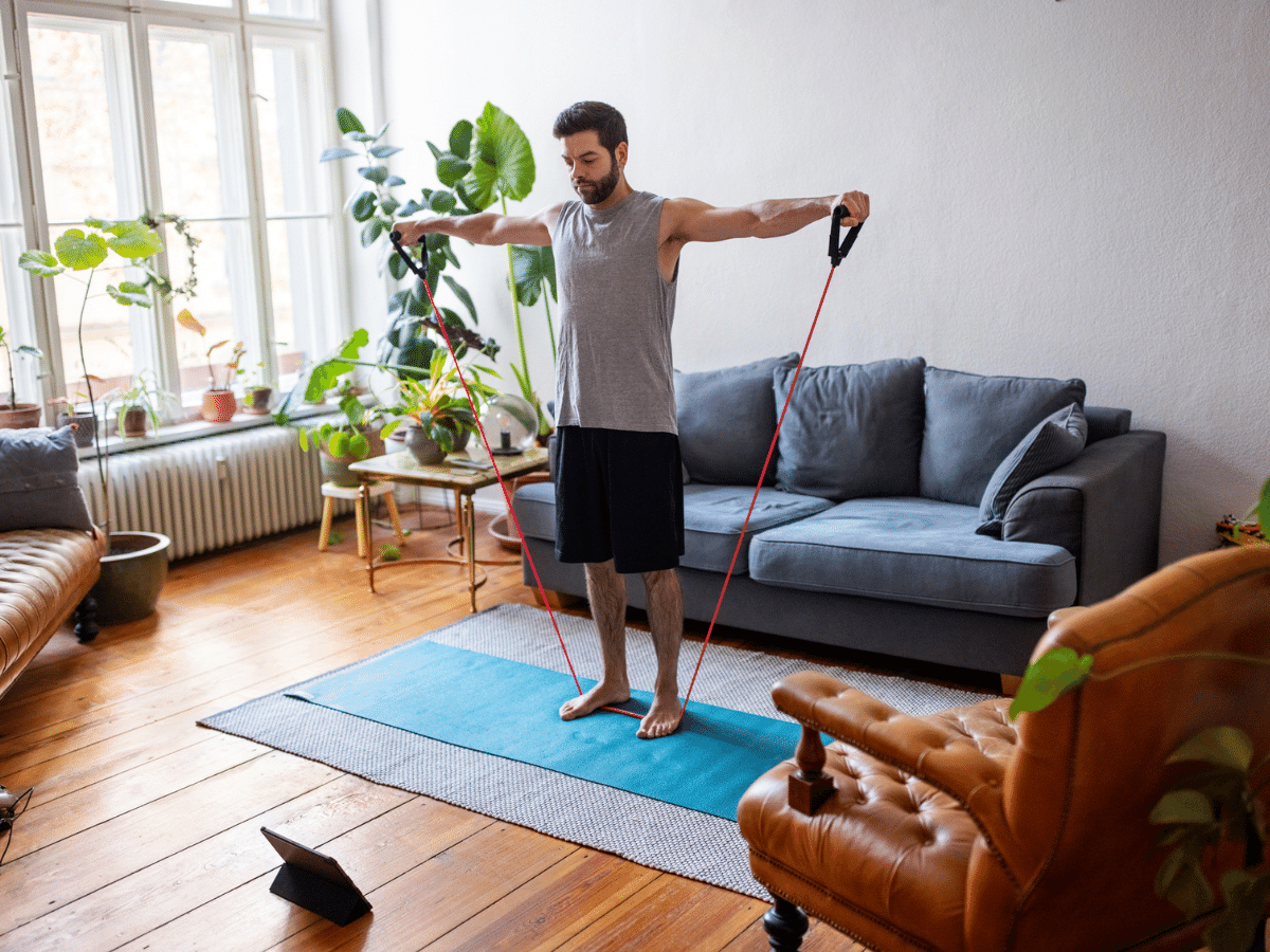 Young man exercising in his living room at home.