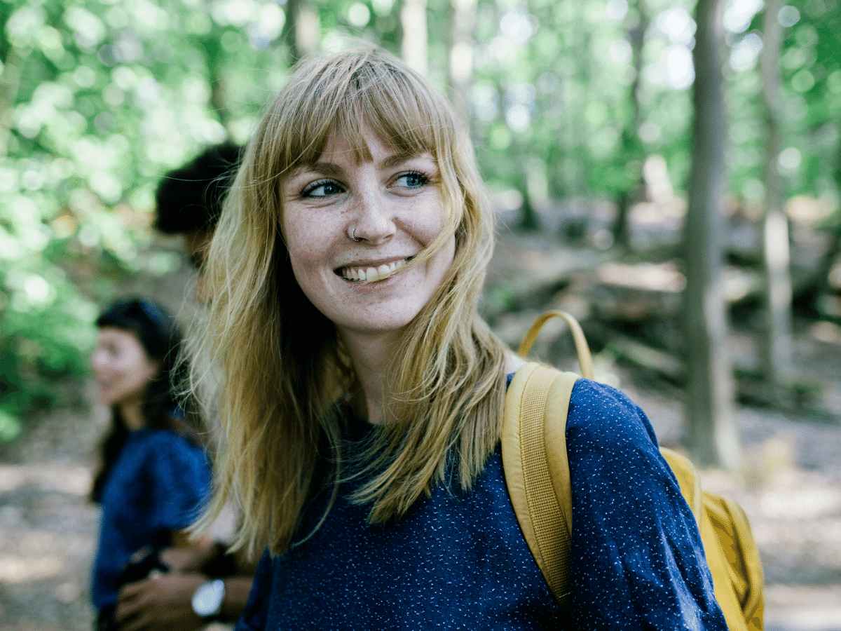 A young woman smiling while on a walk outside with friends.