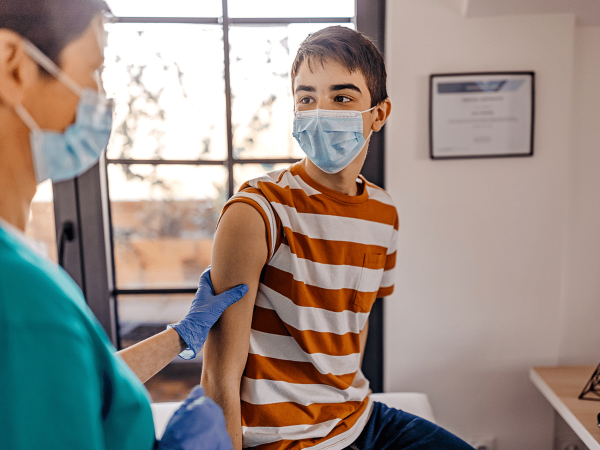 Teenage boy in a doctor's office preparing to receive a vaccine