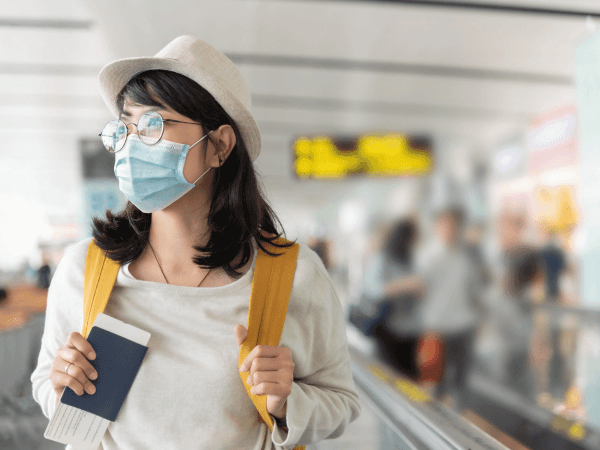 Young woman wearing a mask holding a passport and carrying a backpack at an airport