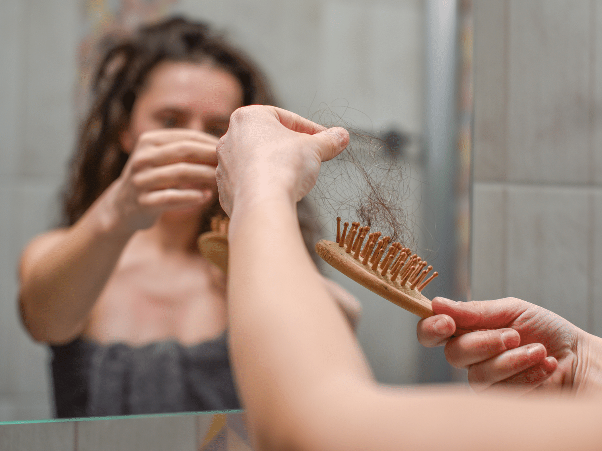 Woman pulling hair out of a hairbrush in the bathroom