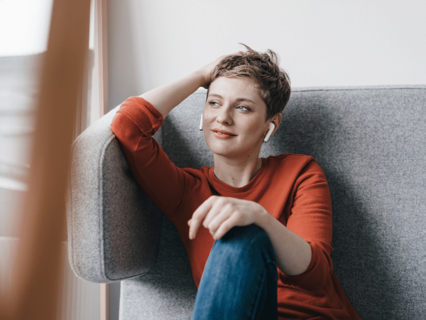 woman sitting on a couch listening to earbuds