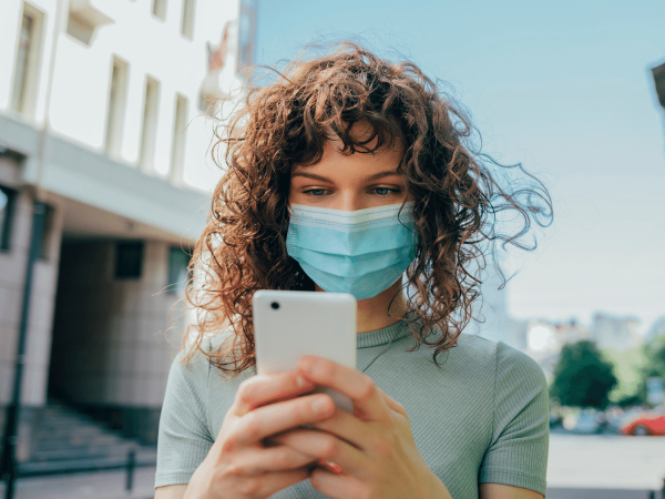 Woman wearing a face mask and reading news on her smartphone
