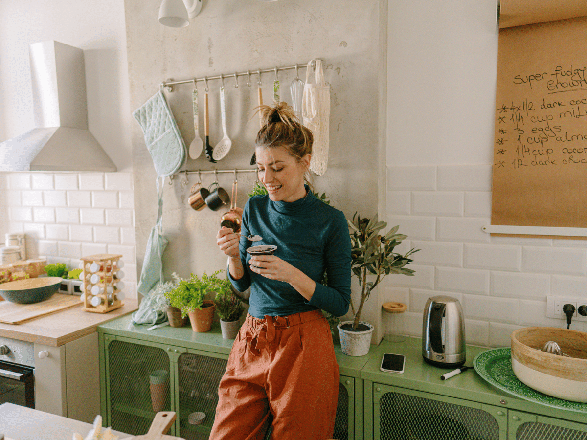 Young woman eating yogurt in her kitchen.