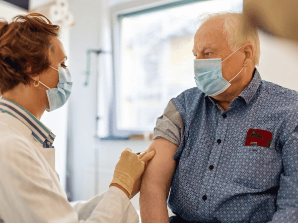 Older man receiving a COVID-19 vaccine in his doctor's office.