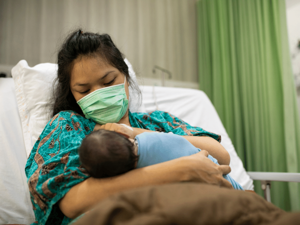 New mother holding her infant in the hospital.