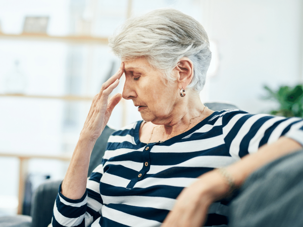 Elderly woman sitting on the couch holding her head in pain