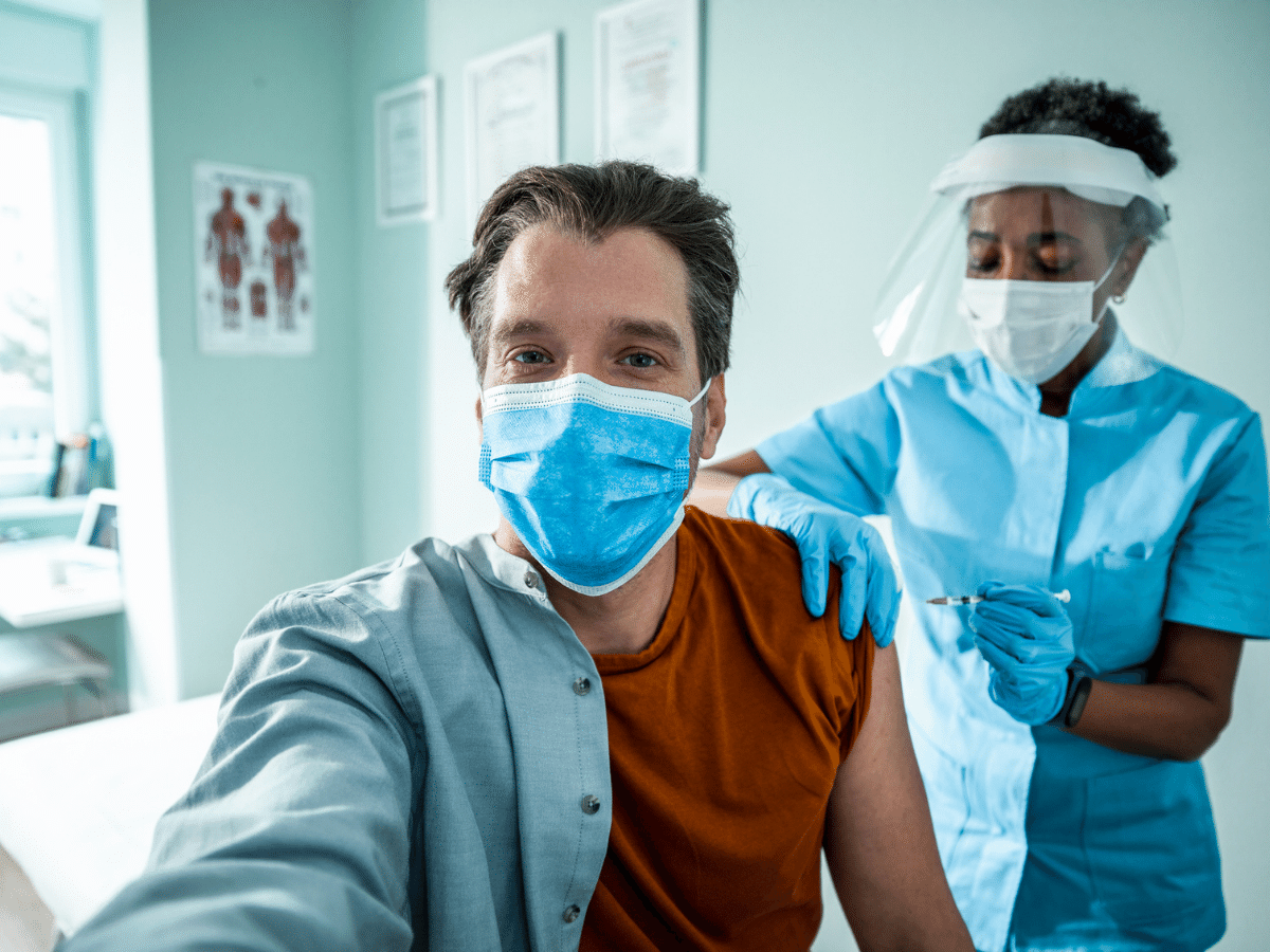 Man takes a selfie as he receives a vaccination.