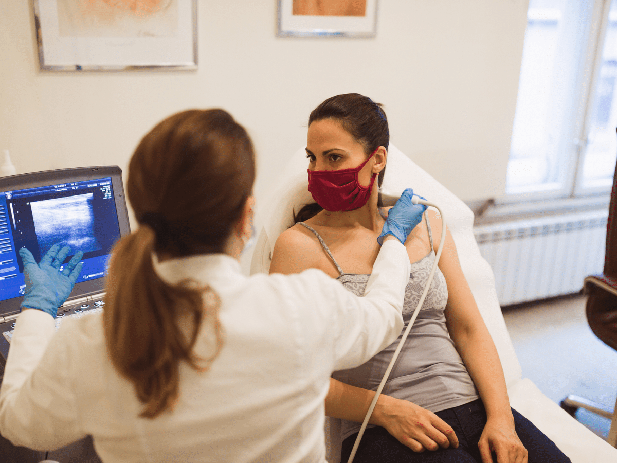 Female doctor using an ultrasound machine on a female patient's neck.