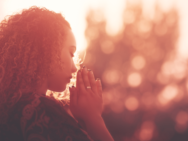 Woman praying with her hands clasped and eyes closed at sunset